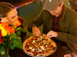 Two customerCouple eating a pizza in the Franciscan Well beer garden where table booking is not required