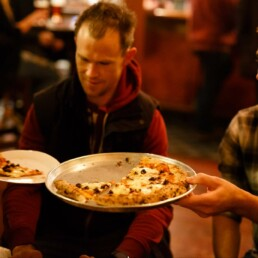 Customers sharing pizzas in the Franciscan Well which doesnt require advance table booking