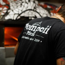 Pizziolo cooking a pizza wearing Pompeii pizza t-shirt