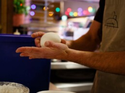 Pizzaiolo rolling a ball of pizza dough in his hands