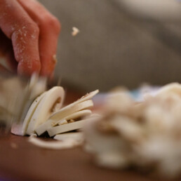 Close-up of staff members hands slicing mushroom pizza toppings