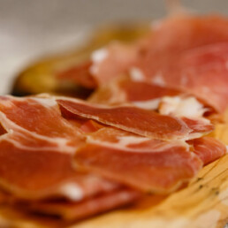 Freshly sliced Parma ham on a wooden board