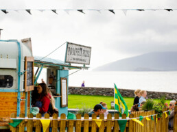 Customers at the Coffee & Gelato food trailer in Waterville, with the Pompeii Pizza mobile pizzeria trailer & sea view in the background