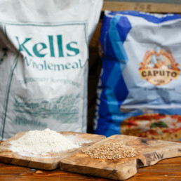 Mound of grain and mound of milled flour on wooden plates with a bag of Kells Wholemeal grain and a bag of Caputo flour in the background
