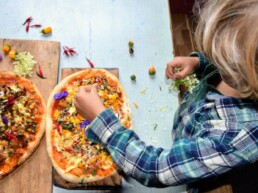 child putting finishing touches on pizza made at home with pompeii pizza kit